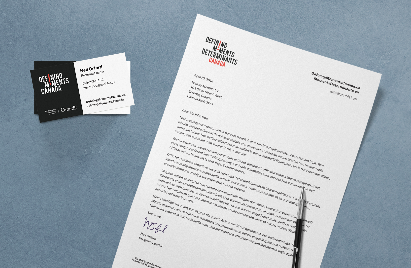 Top view of letterhead and business card designs for Defining Moments Canada